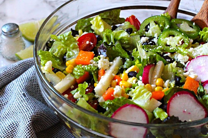 Southwestern Salad Recipe with Black Beans, corn, radishes, jicama, tomatoes served in a glass salad bowl.