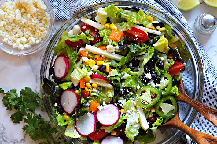 Southwestern salad served in a glass serving bowl with radishes, black beans, corn, jicama, jalapeno rings, cotija cheese.