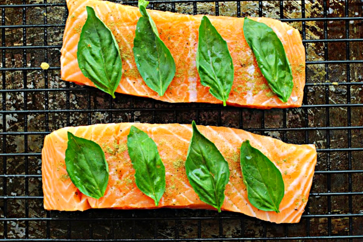 Salmon fillets topped with fresh basil leaves and placed on a sheet pan fitted with a wire grate.