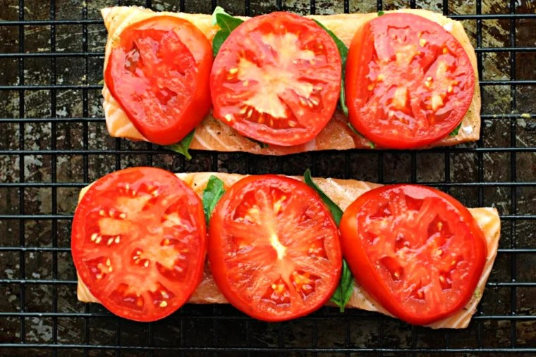 Salmon fillets topped with fresh basil leaves and sliced garden tomatoes, on a sheet pan fitted with a wire grate.