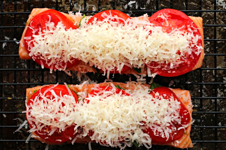 Salmon fillets topped with basil leaves, sliced garden tomatoes and grated parmesan cheese.