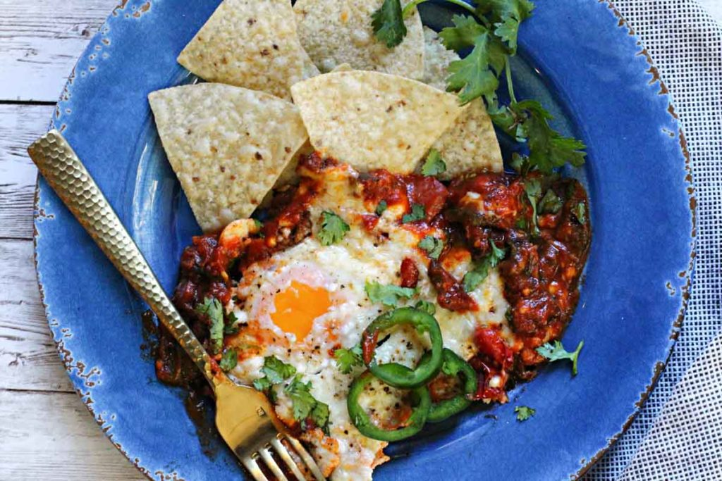 Mexican baked eggs served with tortilla chips and jalapeno peppers