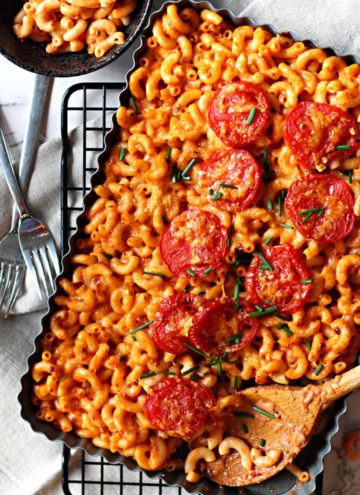 A casserole dish filled with Mexican Macaroni and Cheese topped with sliced tomatoes