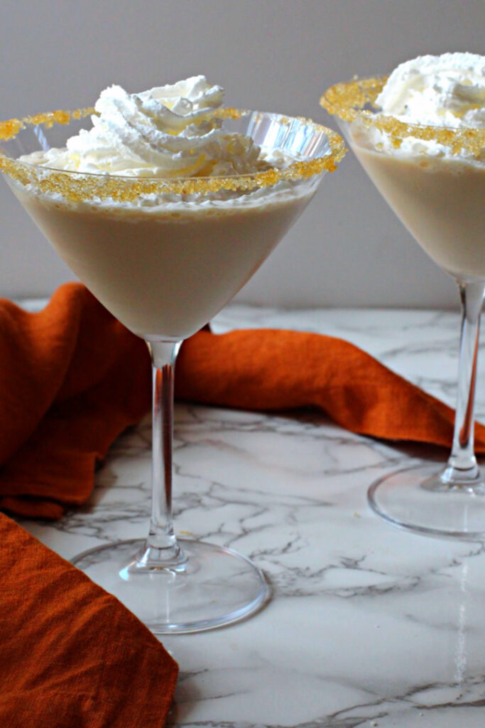 Pumpkin Pie Martini Recipe topped with whipped cream, served in a martini glass rimmed with cinnamon sugar.
