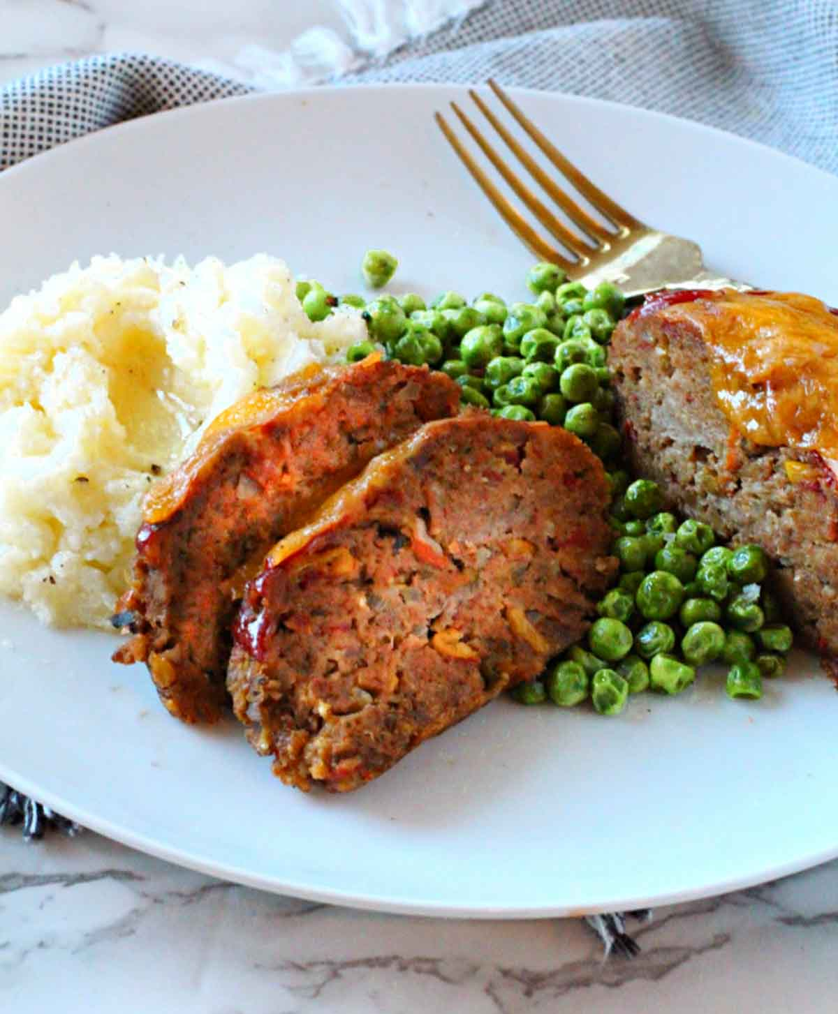 Individual meatloaf recipe for spicy meatloaf. Served on a white plate with mashed potatoes and peas.