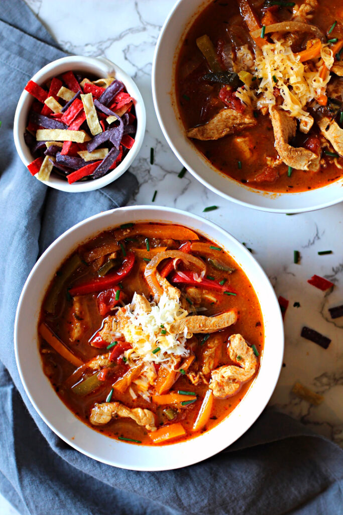 Chicken Fajita Soup topped with grated cheese and tortilla strips