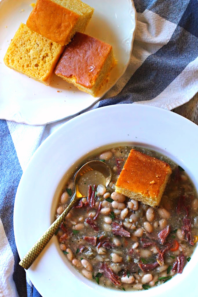 Ham and bean soup served with a slice of cornbread.