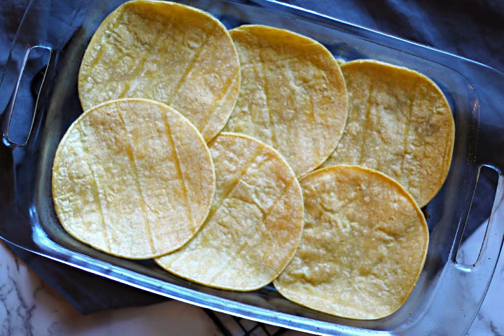 Laying ingredients for Mexican casserole. Corn tortillas in a clear pyrex baking dish.