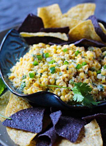 Mexican street corn dip served with blue and white corn tortillas