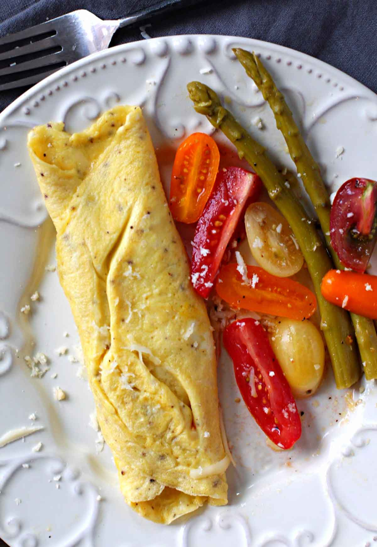 Omelette au fromage, cheese omelette served with sliced petite tomatoes and pickled asparagus