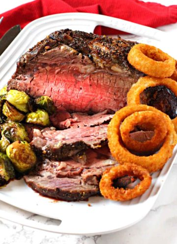 Boneless prime rib roast cooked and served with brussels sprouts and onion rings