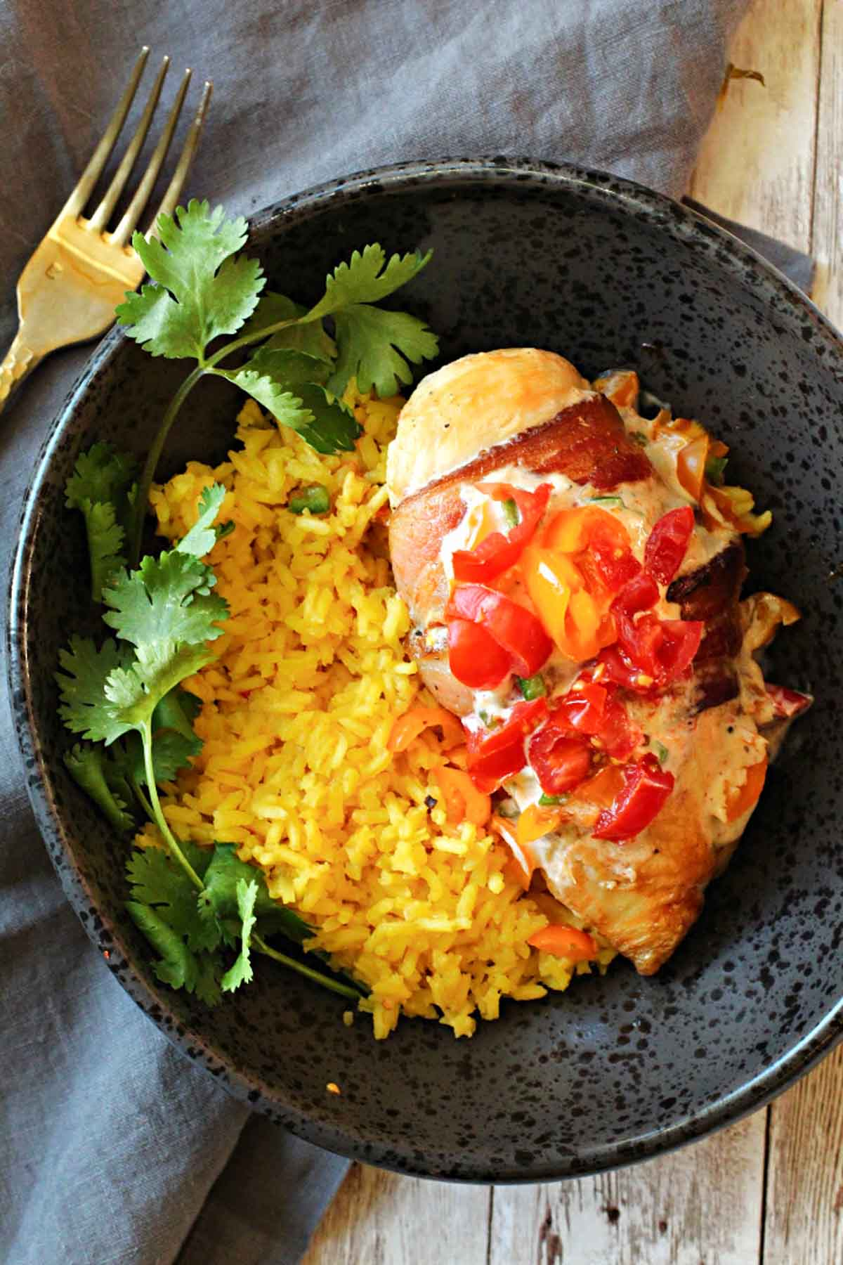 Chicken breast wrapped in bacon topped with a tomato salsa served over yellow mexican rice
