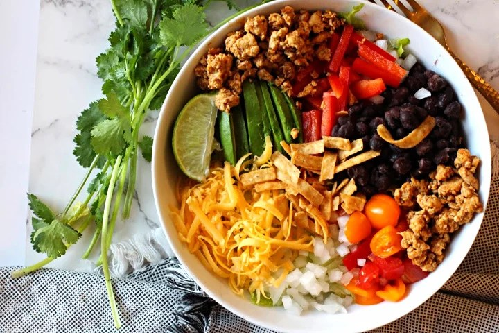 Chicken Burrito Bowl with ground chicken, black beans, sliced avocado, red bell pepper, chopped tomatoes and tortilla strips. With cilantro for garnish.