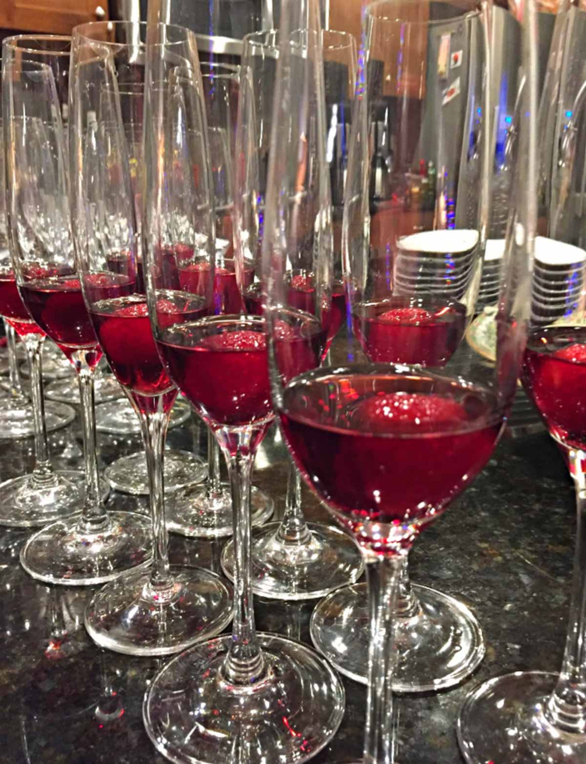 Champaign glasses lined up with chambord and raspberries, for a make ahead christmas cocktail