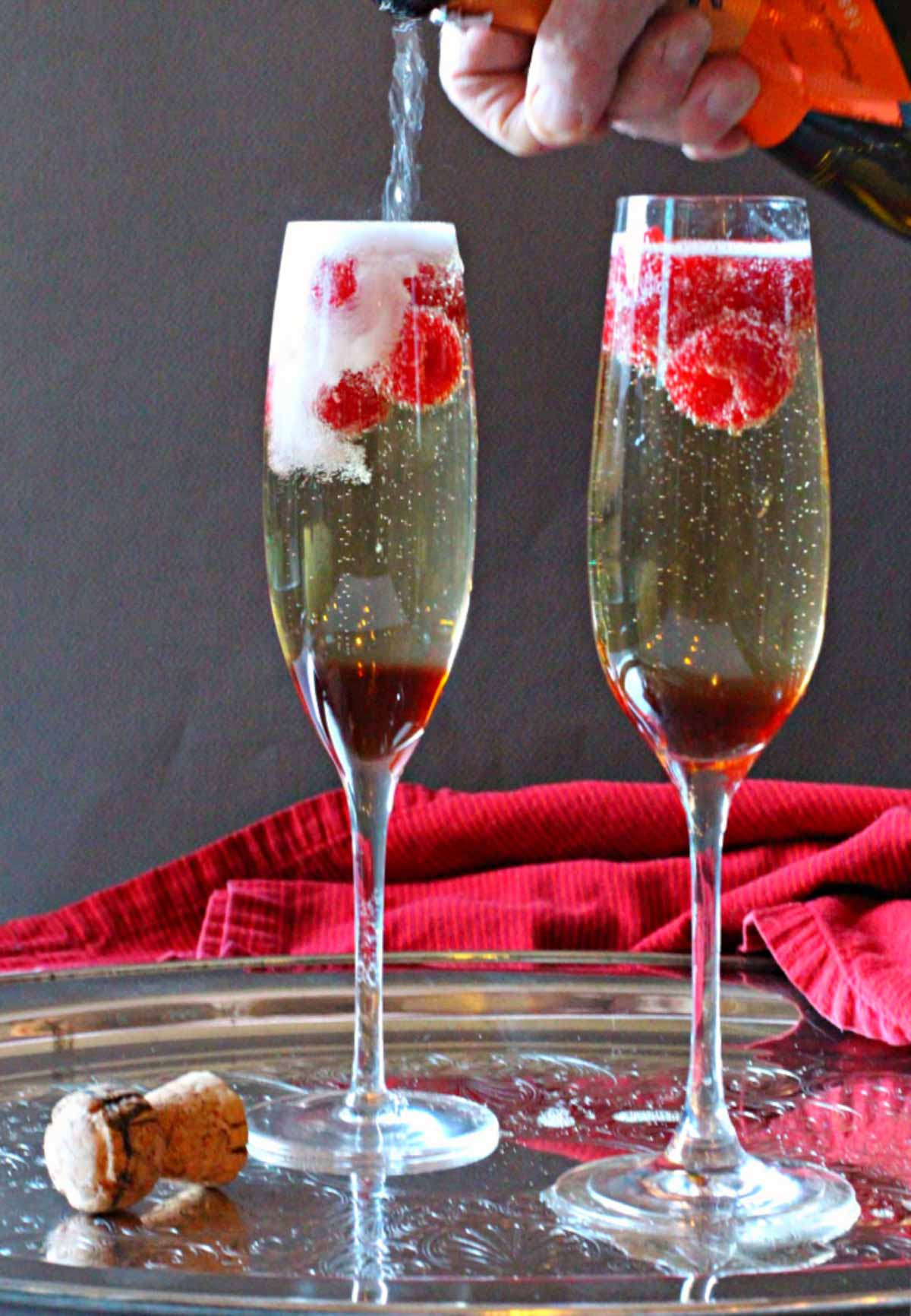 Prosecco Christmas Cocktail made with Chambord Liqueur and fresh raspberries. Served in Champagne flutes.