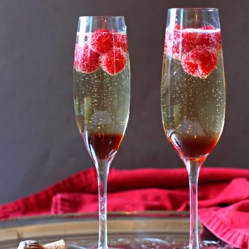 Raspberry Chambord Prosecco cocktail served in two champagne glasses with raspberries.