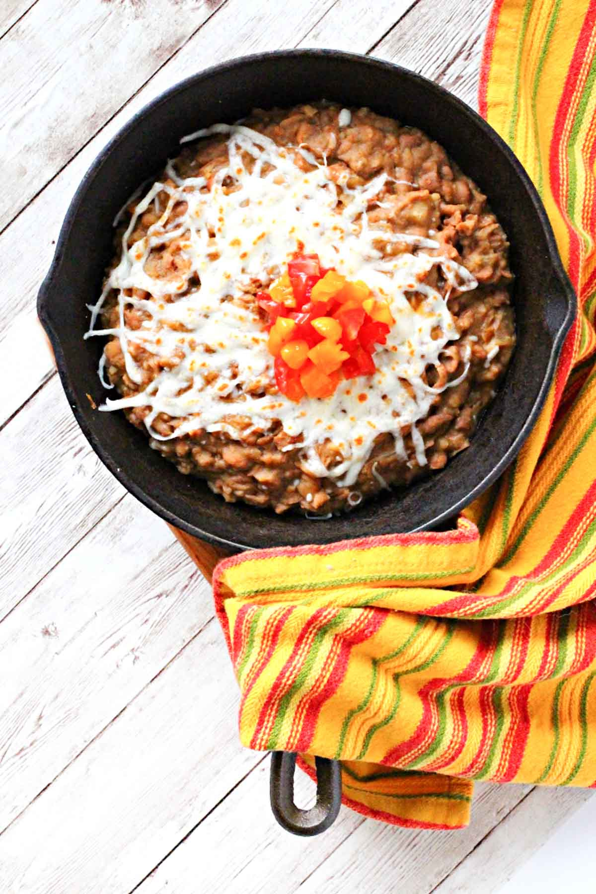 Instant pot refried beans served in a cast iron skillet topped with cheese and chopped tomatoes