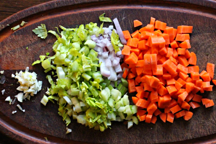 Chopped carrots, shallots, celery and garlic on a wood cutting board