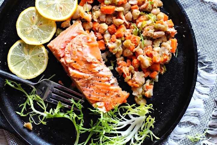 Salmon fillets seared in a cast iron skillet with diced carrots, celery, shallots, garlic and white beans. With slices of lemon and frizee lettuce