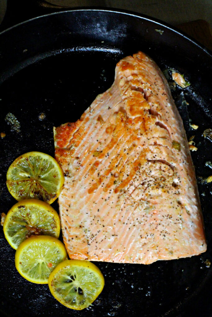A salmon fillet cooking in a cast iron skillet surrounded by lemon slices.