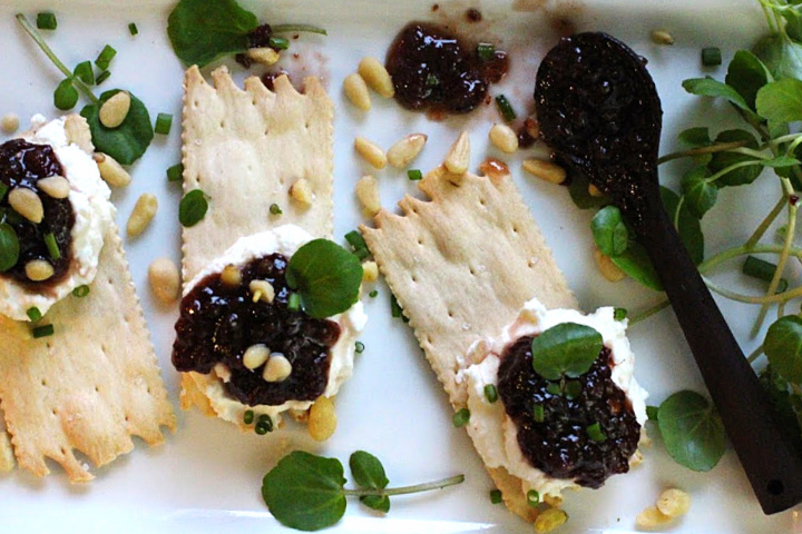 Wafer crackers topped with whipped chevre cheese and Heidi's red chile raspberry jam. On a white platter garnished with pinyon nuts and watercress