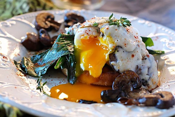 Poached eggs on a toasted english muffin and wilted spinach topped with mushroom cream gravy and thyme
