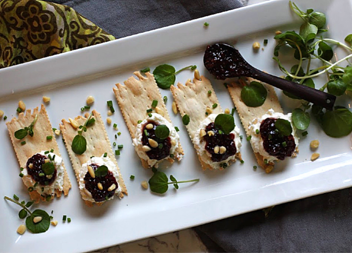 Wafer crackers topped with whipped goat cheese and topped with Heidi's Red Chile Raspberry Jam. Garnished with pinon nuts, chives and watercress. On a white serving platter