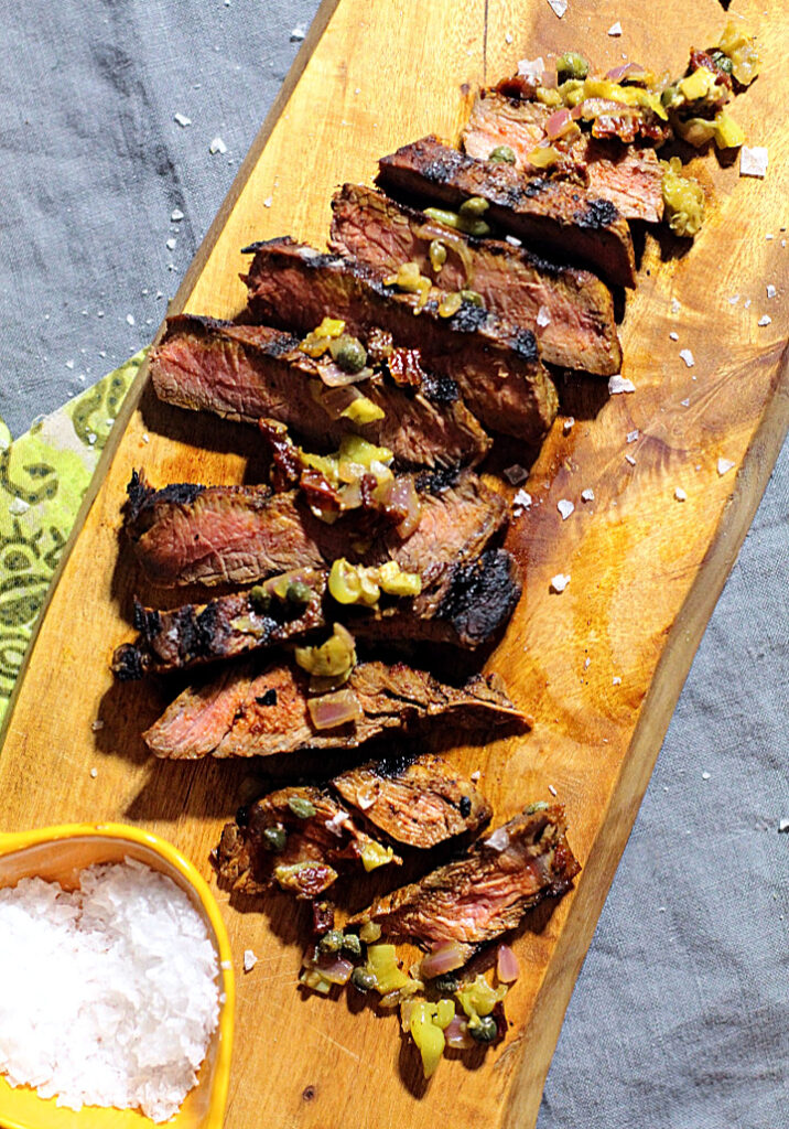 Sliced sirloin steak on a cutting board topped with pepperoncini and caper relish and sprinkled with Maldon sea salt.