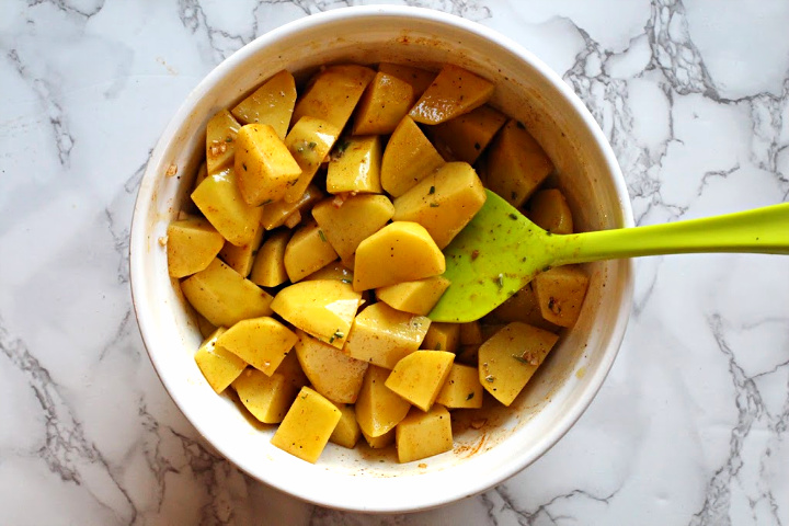 Cubed yukon gold potatoes coated with seasonings for cask iron skillet oven roasted potatoes