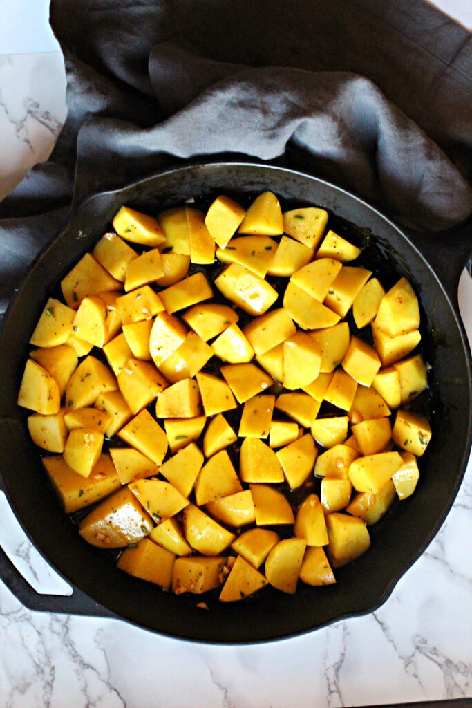 Cubed Yukon gold potatoes in a cast iron skillet to make oven roasted potatoes