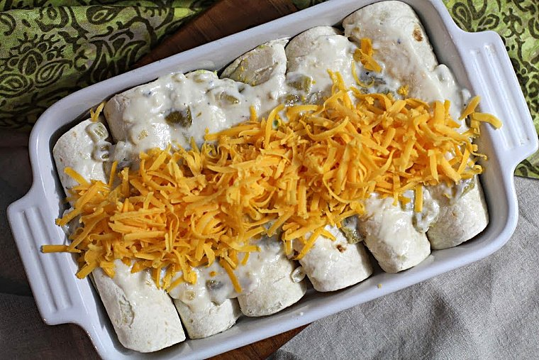Avocado and scrambled egg breakfast burritos in an oven proof casserole dish topped with shredded cheese