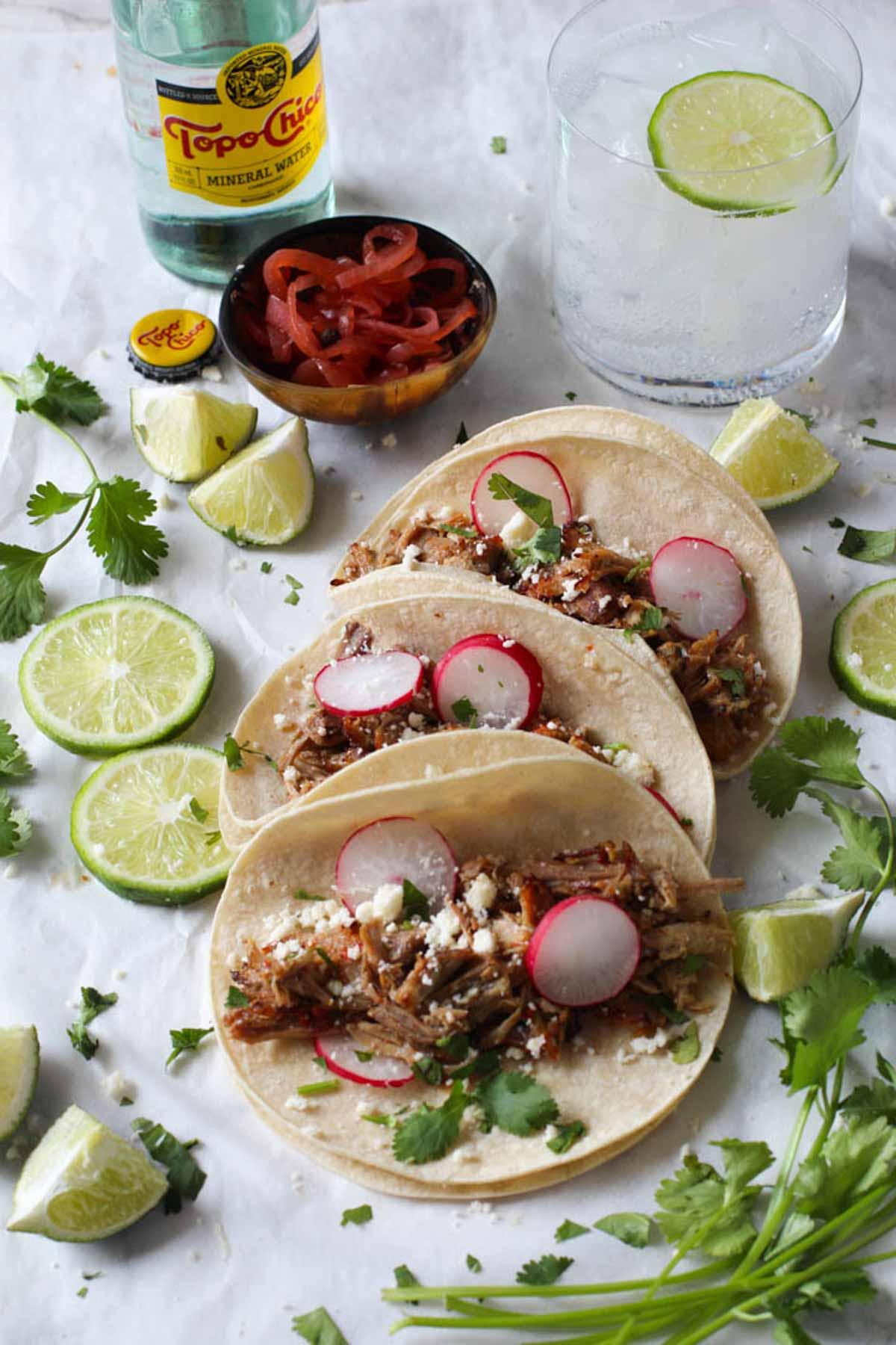 3 pork carnitas tacos garnished with slices of radish, lime served in corn tortillas