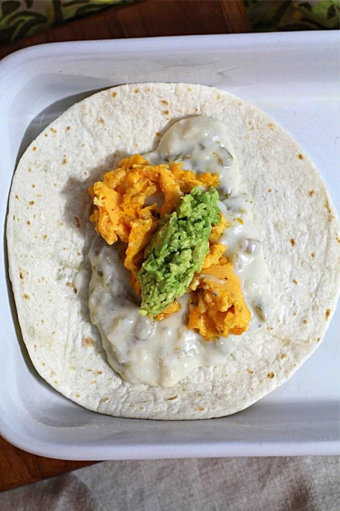 Building a scrambled egg smashed avocado green chile breakfast burrito