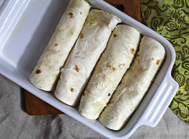Avocado and scrambled eggs burritos in an oven proof baking dish