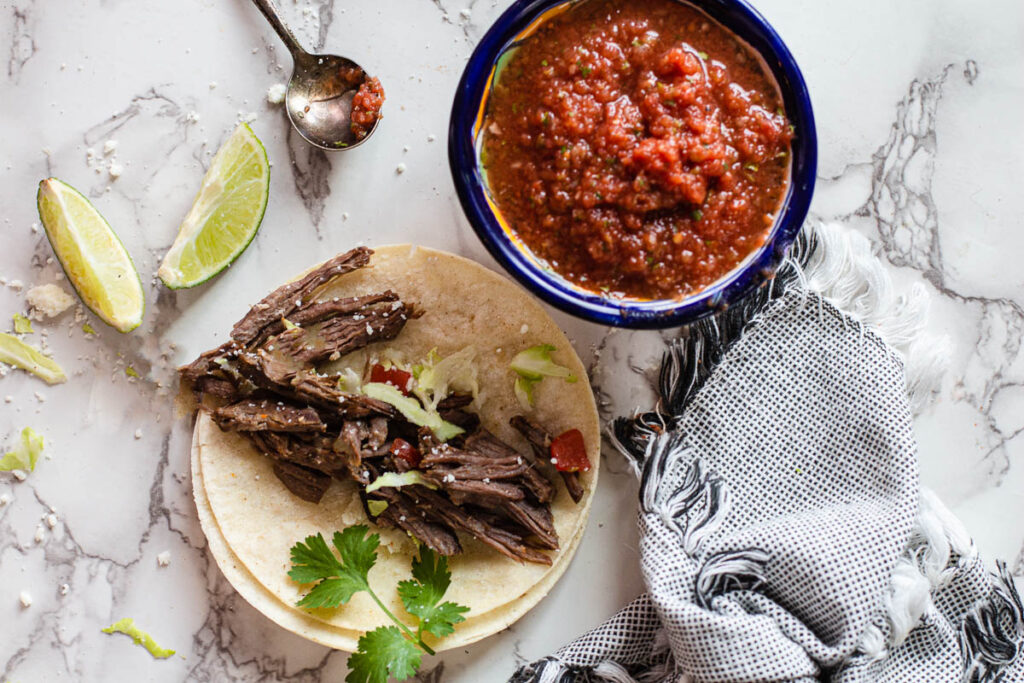 Crockpot roast beef tacos with cabbage limes and salsa
