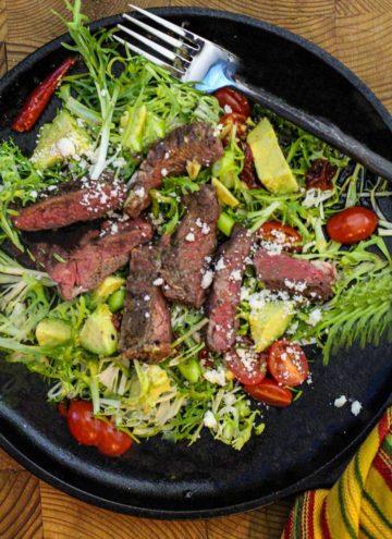 Skirt steak salad on a bed of fancy greens with cherry tomatoes and crumbled cheese