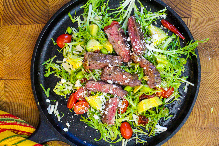Skirt steak salad served on a cast iron comal with frisee topped with tomatoes, avocado and chipotle dressing