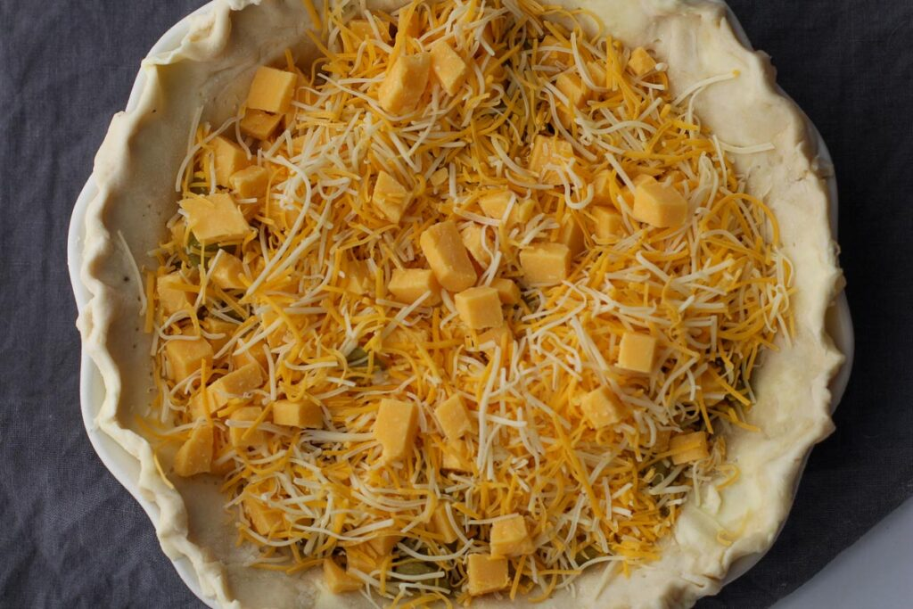 Cubed cheddar cheese and shredded cheese to make a quiche