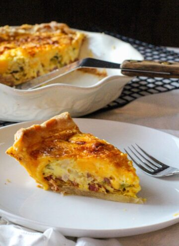 A slice of hatch green chile bacon quiche with a deep dish pie pan with quiche and spatula
