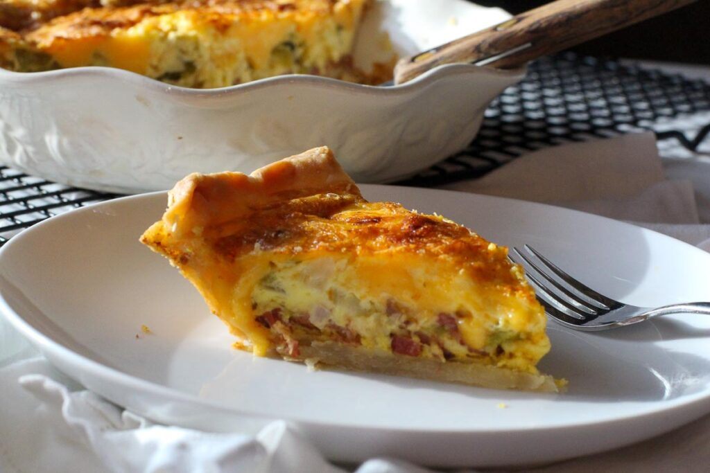 A slice of green chile bacon quiche on a white plate