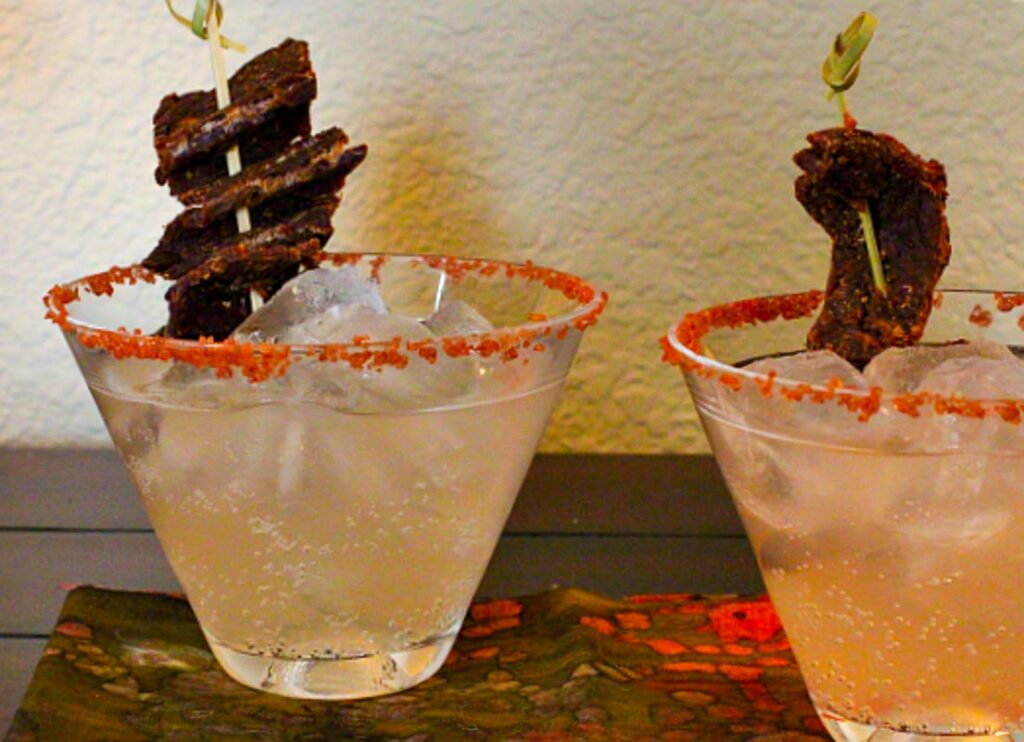 Two cocktail glasses holding salty dog cocktails with beef jerky for garnish.
