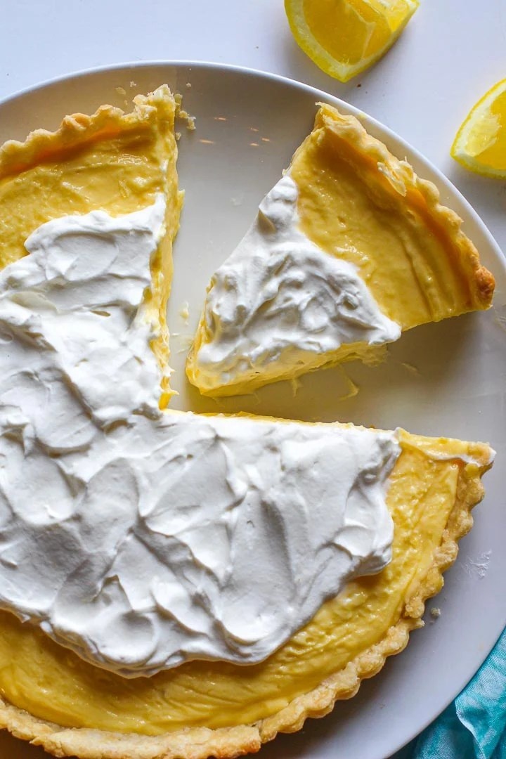No Bake lemon dessert tart topped with whipped cream with a slice cut out.