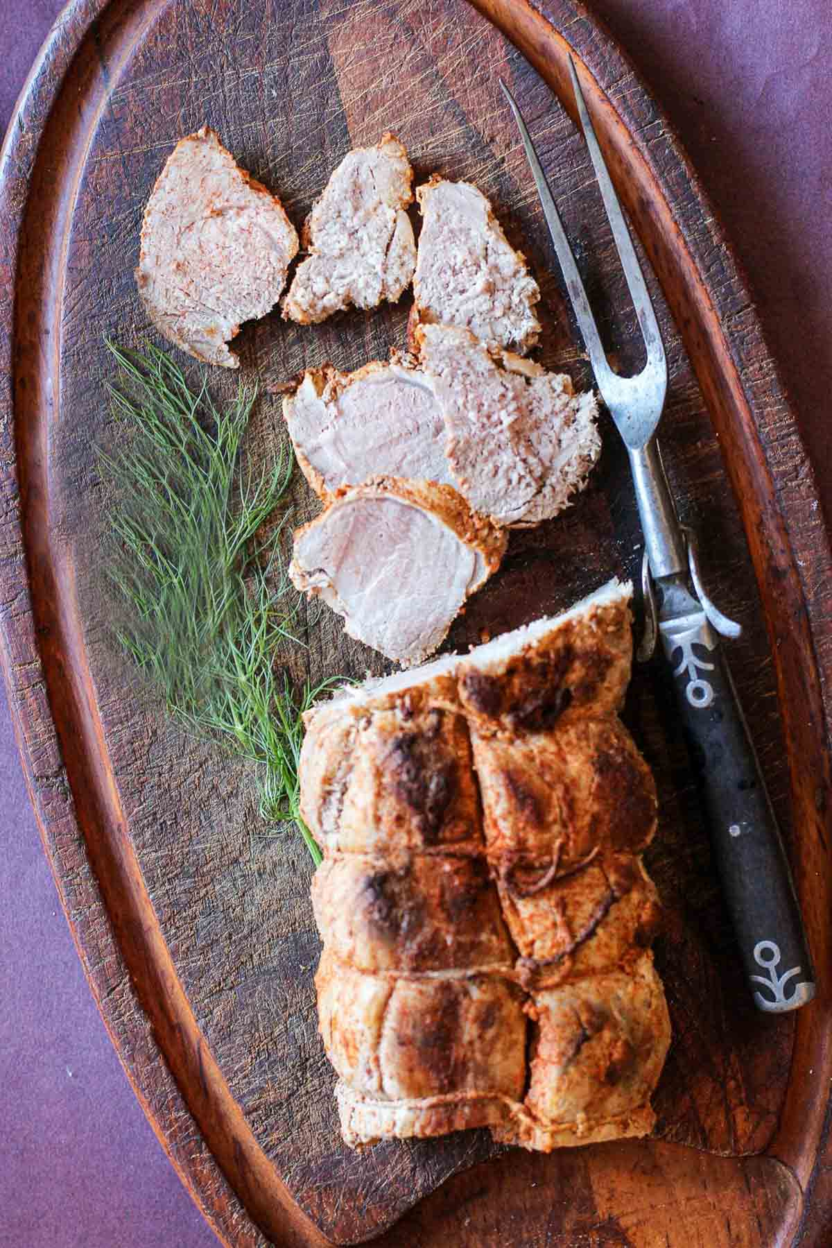 Pork tenderloin sliced on a cutting board that's been rubbed with cooking spices