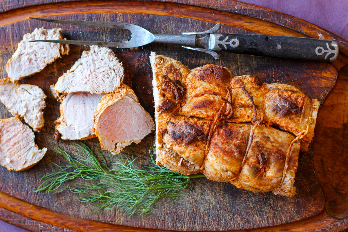 Two pork tenderloins tied together, oven roasted and sliced on a wooden cutting board