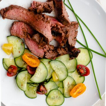 Asian marinade for grilled flank steak served with asian cucumbers and garnished with chives