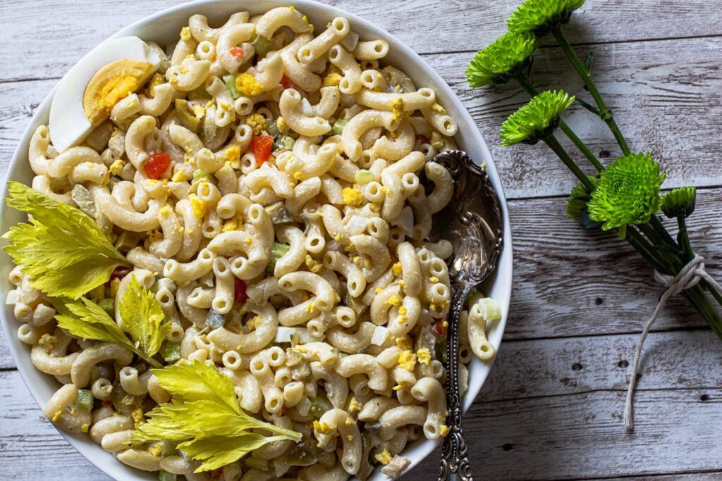 Classic macaroni salad with mayonnaise, celery, onion and green olives garnished with celery leaves and hard boiled egg