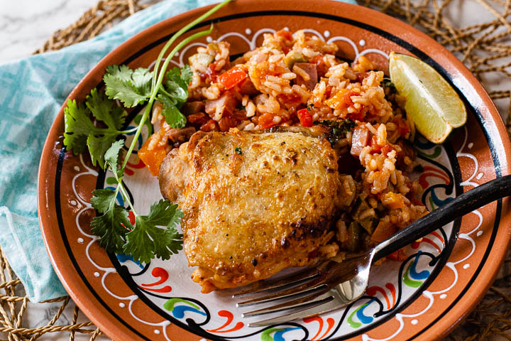 Fried chicken thigh served along siMexican rice and garnished with cilantro and lime wedge.