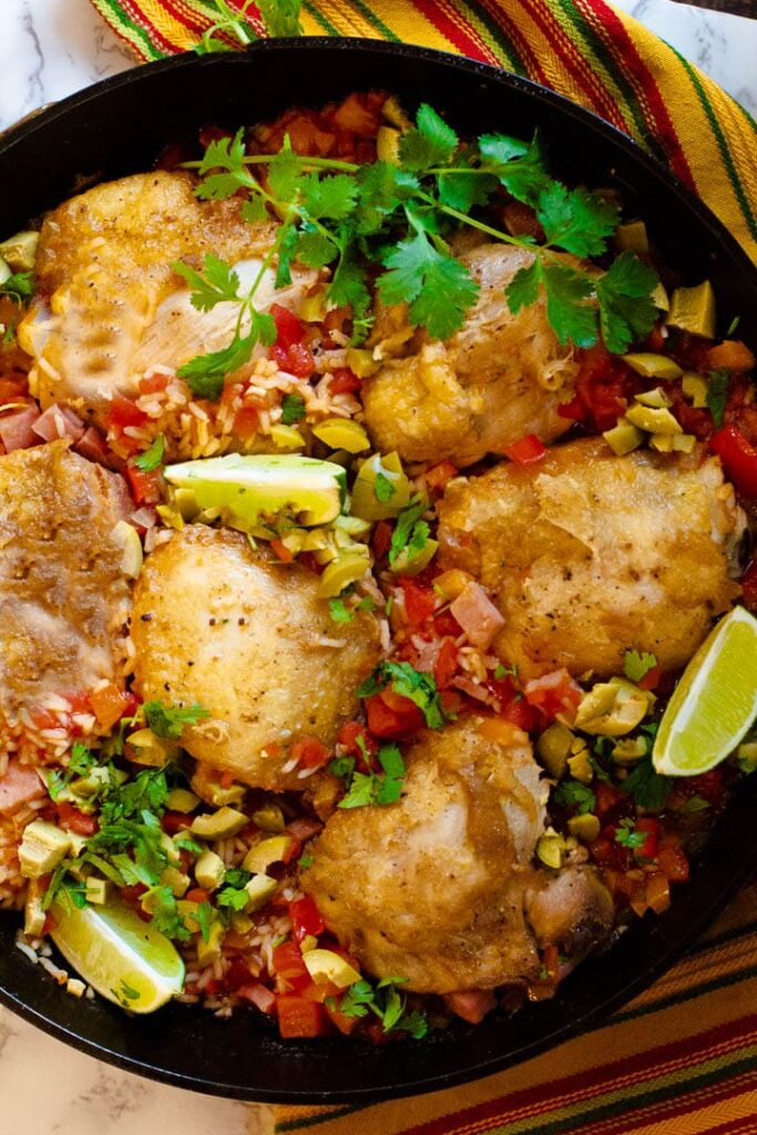 Mexican chicken and rice in a cast iron skillet garnished with cilantro and green olives