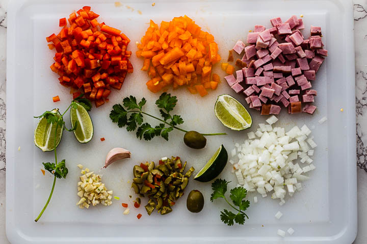 Arroz con Pollo ingredients. Chopped bell peppers, chopped ham, chopped onions, chopped green olives, chopped garlic and cilantro