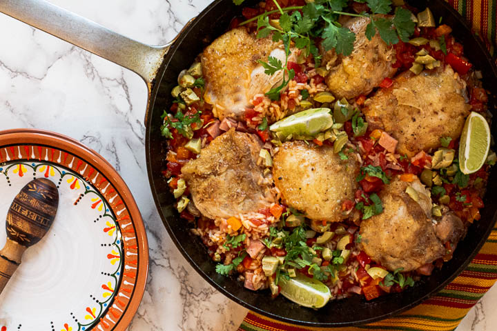 Arroz con Pollo, Mexican chicken and rice using chicken thighs cooked in a cast iron skillet garnished with lime wedges, cilantro and green olives.